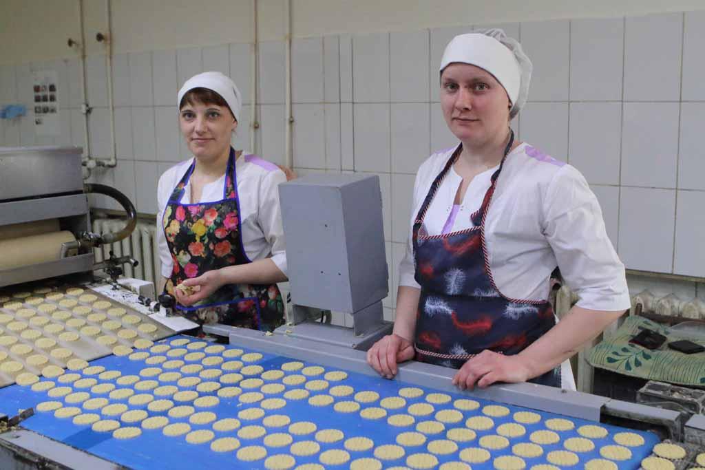 Пекари-кондитеры Светлана Мазур и Елена Ковшикова закладывают тесто в ёмкость, из которой оно распределяется по формочкам, после чего заготовки дви-жутся по конвейеру. Печенье с неровными краями не пройдет мимо внимательных глаз пекарей.