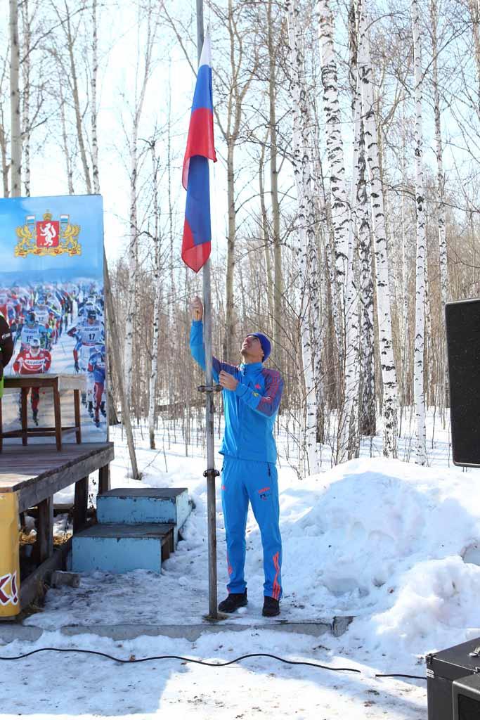 Флаг России поднимает мастер спорта международного класса, член национальной сборной России по лыжным гонкам Евгений Белов.