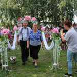 Через цветочную арку проходят Анатолий и Лидия Котовы. Они прожили вместе 50 лет и на мероприятии были награждены знаком отличия Свердловской области «Совет да любовь».