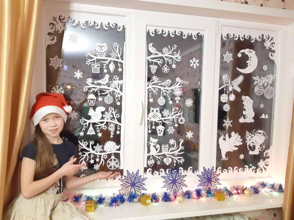 Создать такую красоту на окнах Светлане Машковцевой помогали дочки Яна и Лиза, и даже бабушка Зоя. Дети и бабушка вырезали где полегче, а Светлана – где посложнее. На всё ушло около месяца. «Мы просто хотели создать праздничное настроение. Каждый год семьёй украшаем окна, детям очень нравится этот увлекательный процесс» – делится Светлана. На фото Яна Машковцева.